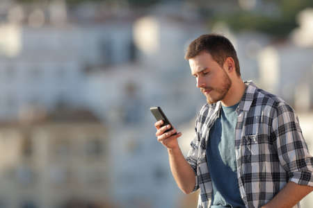 Serious man checking text on smartphone in a town on vacation