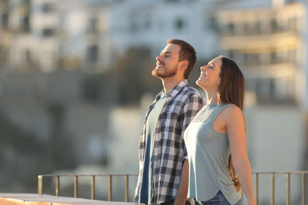 Side view portrait of a happy couple breathing fresh air in a town street