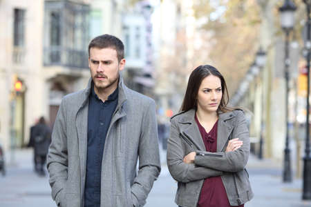 Front view portrait of an angry couple walking in the street after argument