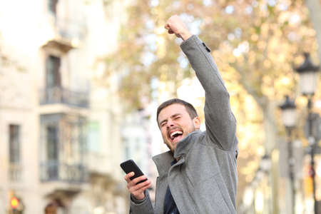 Portrait of an excited man holding smart phone and raising arm in the street