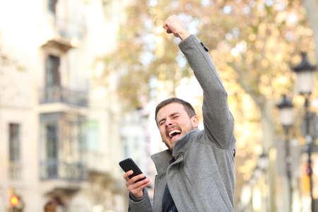 Retrato de un hombre emocionado sosteniendo un teléfono inteligente y levantando el brazo en la calle Foto de archivo