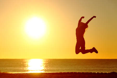 Baklight silhouette of a happy girl jumping on the beach at sunset Stock Photo