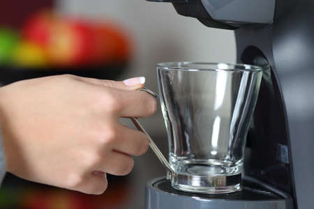 Close up portrait of a woman hand holding an empty cup in a coffee maker