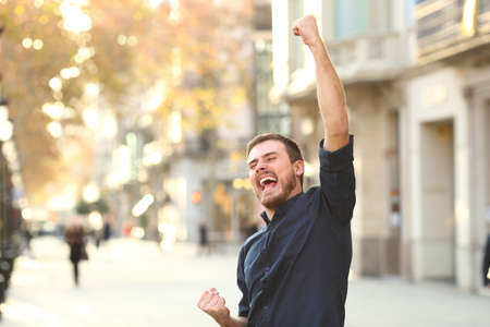 Excited man raising arms celebrating sucess in the middle of the street
