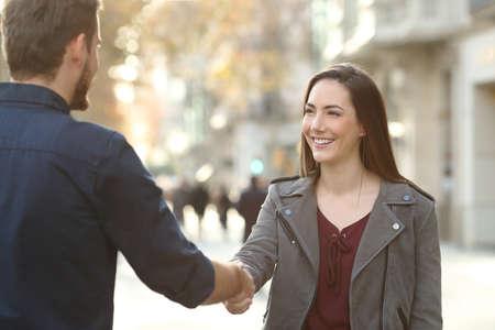 Heureux homme et femme accord concluant une poignée de main dans une rue de la ville