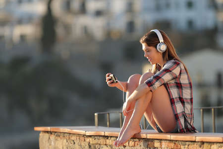 Happy teenage girl watching video on a smart phone sititng on a ledge in a town at sunset Stock Photo