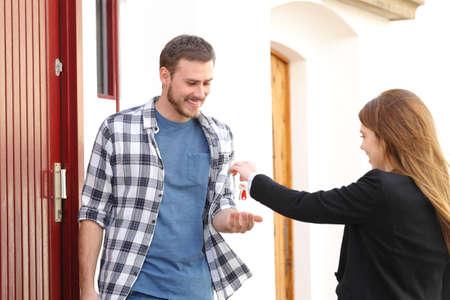 Glücklicher Mieter, der Wohnungsschlüssel vom Immobilienmakler auf der Straße erhält