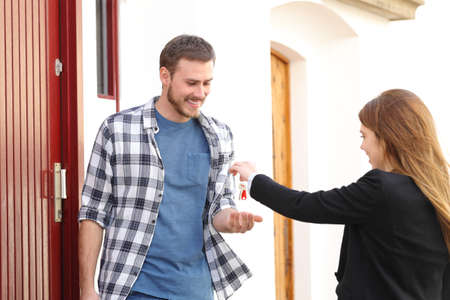 Happy renter receiving apartment keys from real estate agent in the street Standard-Bild - 115370827