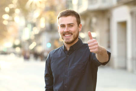 Front view portrait of a happy man in the street gesturing thumbs up