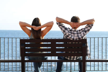 Back view of a happy couple relaxing sitting on a bench contemplating ocean on the beach Stock Photo