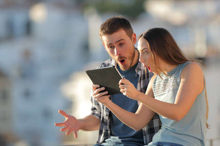 Amazed friends finding online content on a tablet outdoors in a town at sunset 版權商用圖片 - 115370844