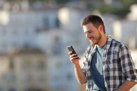 Happy man checking smart phone text in a town at sunset
