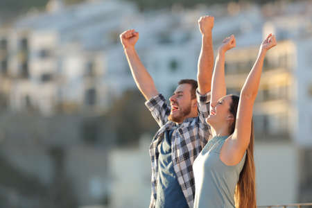 Excited couple celebrating vacation raising arms in a town at sunset