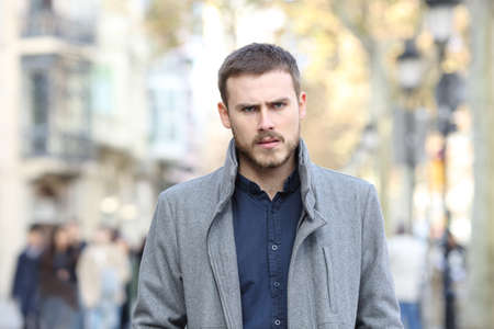 Front view portrait of an angry man walking in the street looking at camera
