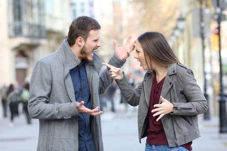 Pareja enojada discutiendo en medio de una calle de la ciudad Foto de archivo