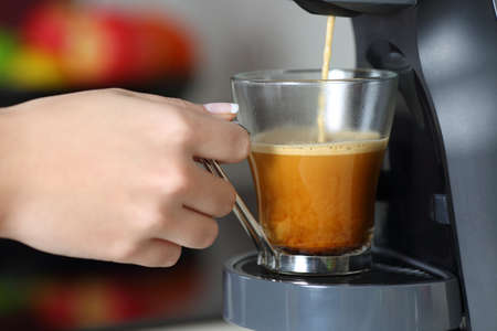 Close up of a woman hand using a coffee maker