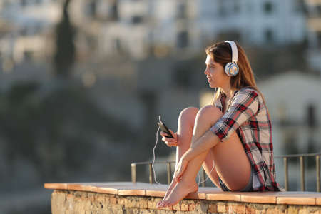 Relaxed teenage girl listening to music sitting on a ledge in a town outskirts