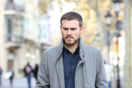 Front view of an angry man walking towards camera in the street Stock Photo