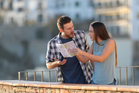 Angry couple arguing about travel destination on vacation in a town Banque d'images - 115370903