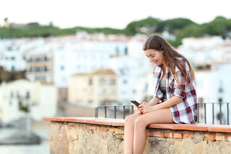 Happy girl checking smart phone content sitting on a ledge in a coast town Stock Photo