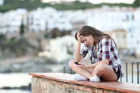 Full body portrait of a worried girl checking smart phone content sitting on a ledge in a coast town