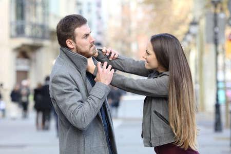 Retrato de vista lateral de una pareja enojada peleando en la calle Foto de archivo
