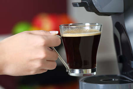 Close up portrait of a woman hand holding a mug in a coffee maker Stock Photo