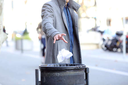 Close up of a man hand throwing paper into trash bin in the street Stock Photo