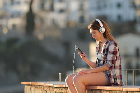 Relaxed girl listening to music with smart phone sitting on a ledge at sunset in a town