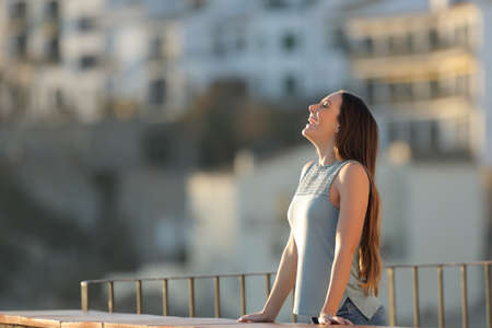Happy woman in a town breathing fresh air from a rural apartment balcony Standard-Bild
