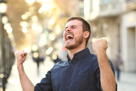Portrait of an excited guy celebrating success in a city street