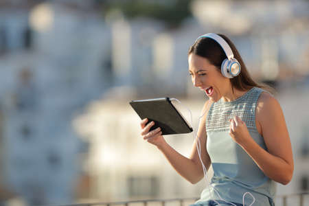 Excited woman finding media offers on a tablet sitting in a town at sunset
