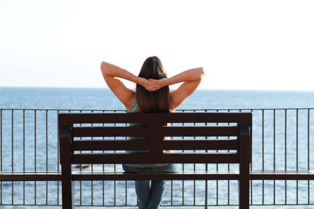 Back view portrait of a woman relaxing on the beach sitting on a bench contemplating ocean