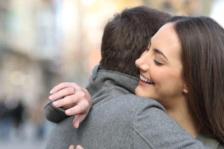 Coppia abbracciarsi dopo la proposta di matrimonio e la fidanzata guardando l'anello di fidanzamento in strada