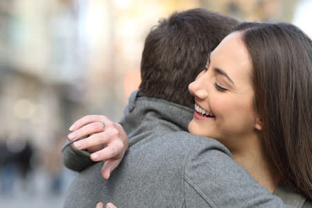 Couple hugging after marriage proposal and girlfriend looking at engagement ring in the street