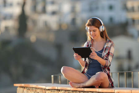 Teenager listening and watching tablet online content outdoors in a town outskirts at sunset 版權商用圖片