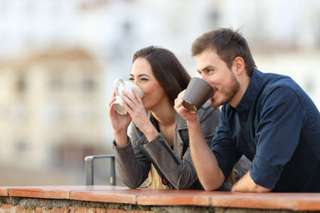 Happy couple drinking coffee contemplating views outdoors in a town outskirts Stock Photo