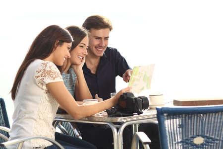 Three happy tourists checking guide sitting in a coffee shop on vacation