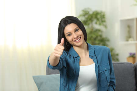 Front view portrait of a happy lady gesturing thumb up sitting on a couch at home