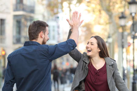 Two excited friends or couple giving high five in a city street Foto de archivo
