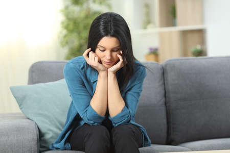 Pensive woman looking down sitting on a couch in the living room at home Stock Photo