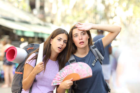 Two backpackers suffering heat stroke walking on the street and fanning on summer vacation Stockfoto - 116123646