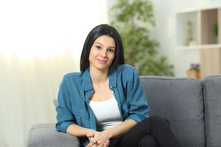 Relaxed woman posing looking at camera sitting on a couch in the living room at home 写真素材