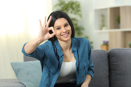 Front view portrait of a happy woman gesturing ok sign sitting on a couch at home