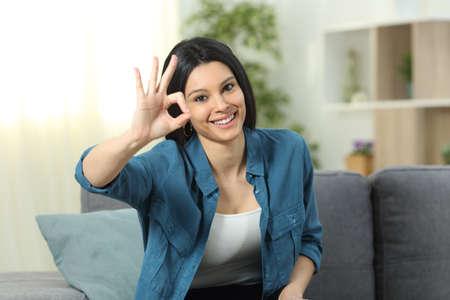Vista frontal retrato de una mujer feliz gesticulando signo ok sentado en un sofá en casa