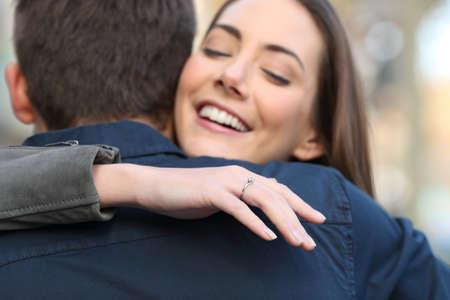 La ragazza felice guarda l'anello di fidanzamento che abbraccia il suo ragazzo dopo la proposta di matrimonio