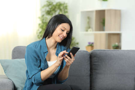 Happy woman using a smart phone sitting on a couch in the living room at home