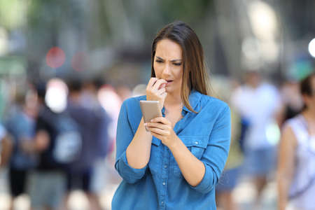 Nervous woman biting nails checking smart phone content standing in the street