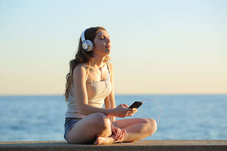 Full body portrait of a girl relaxing listening to music from smart phone sitting on a bench on the beach