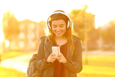 Front view portrait of a happy teenage girl at sunset listening to music from smart phone 免版税图像
